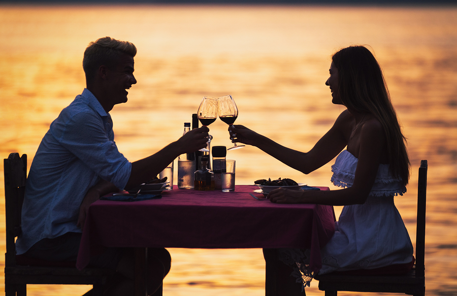 Young romantic couple toasting during dinner on tropical vacation