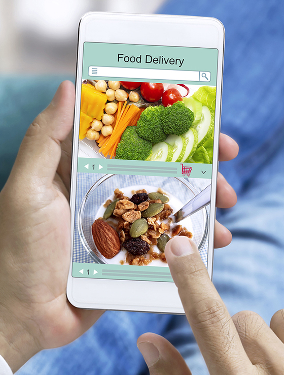 Online order food and express delivery service food shopping concept on touch screen which hand's man holding smart phone lying on sofa at home background.