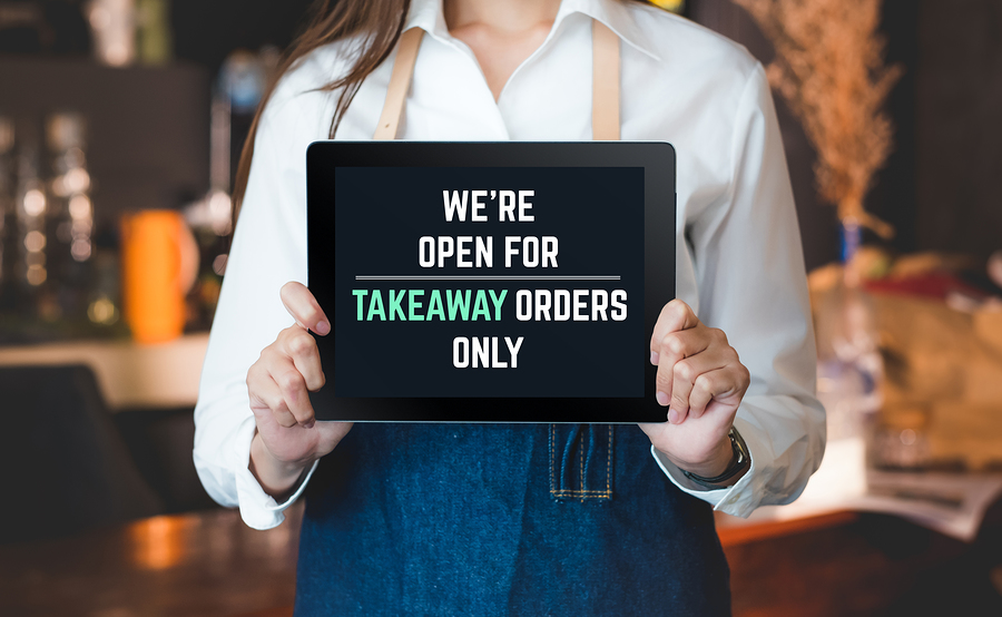 tabblet sign were open for takeaway orders only infront of counterbar social distancing