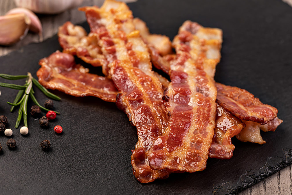 Closeup of slices of crispy hot fried bacon