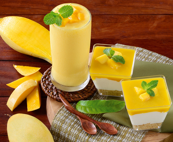 Fresh smoothie mango juice and mango panna cotta with mango slice put on wooden plate and wooden background, homemade cuisine.